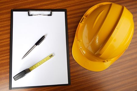 autocad: yellow helmet and notepad on a table Stock Photo