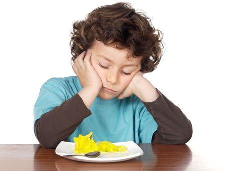 over eating: child eating boring food a over white background