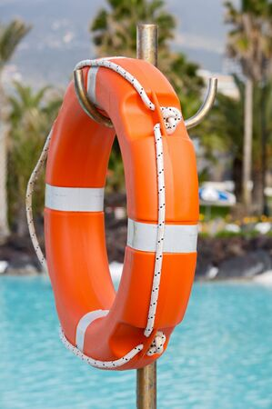 Lifebuoy in a pretty swimming pool with the blue water Stock Photo
