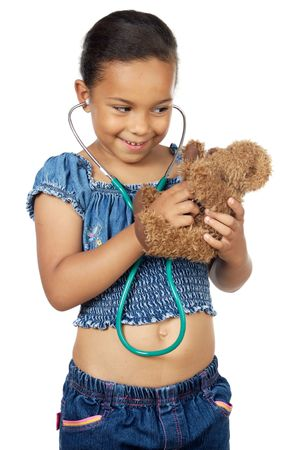 doctor toys: Little doctor examining her bear a over white background