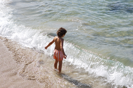 adorable boy playing in the beach over a white background photo