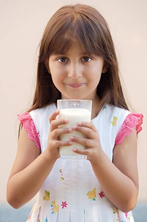 photo of a adorable girl drinking milk  photo