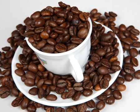 caffiene: Coffee beans in a cup (focus in the first plane)