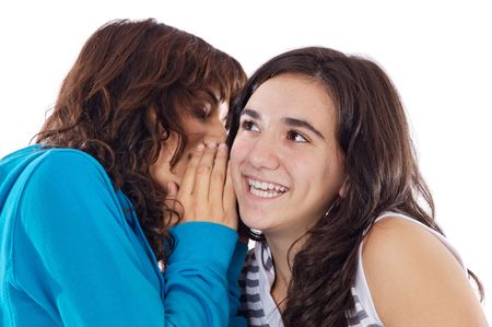 confide: Two teenager girls whispering a secret to the ear
