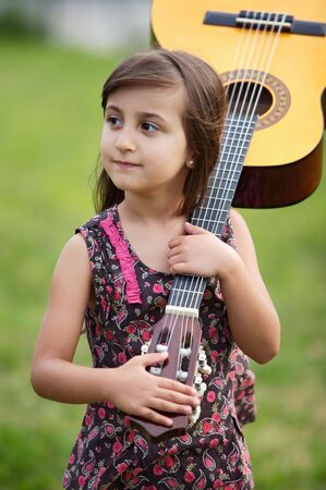 spanish girl: Girl with a guitar on the green grass