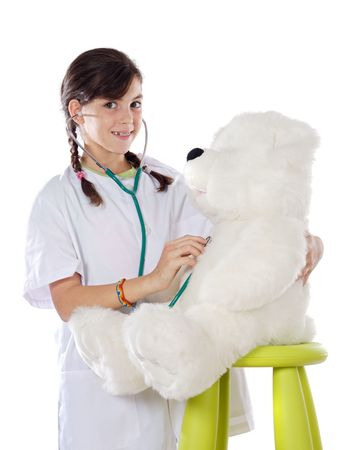 Little doctor examining her bear over white background photo