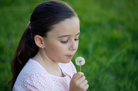 A pretty girl blowing dandelion in the grass photo