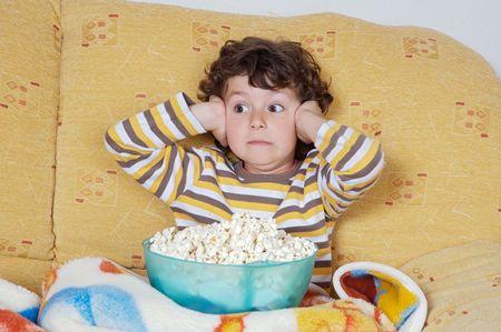 ver television: Kid miedo viendo una pel�cula comiendo palomitas de ma�z