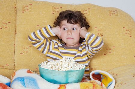 Kid watching a scary movie eating pop corn Stock Photo