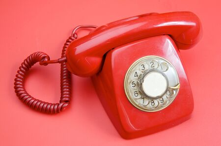 communicated: An old red telephone over red background