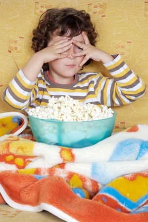 televisor: Kid watching a scary movie eating pop corn Stock Photo
