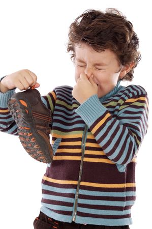 Cute young boy with stinky shoe pitching his nose photo