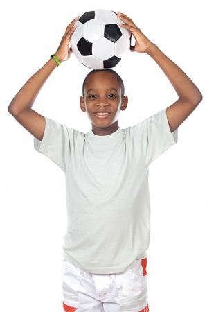 young cute boy holding a soccer ball over his head photo