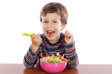 over eating: Child eating salad a over white background