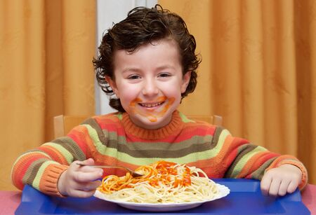 Adorable child eating in his house - focus in the face - photo