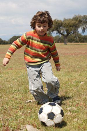jugando futbol: Ni�o peque�o que juega al balompi� - profundidad del campo corta - Foto de archivo