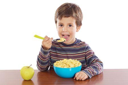 comiendo cereal: Ni�o comiendo su desayuno en un fondo blanco Foto de archivo