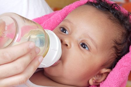 Adorable baby drinking a bottle - focus in the face - Stock Photo - 2514218