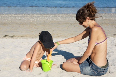 Child and woman playing on the beach photo