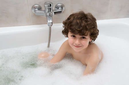 Small child happy and smiling in the bath photo