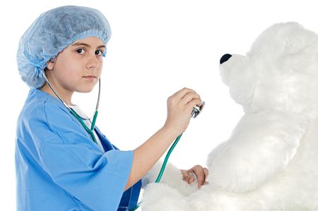 Little doctor examining her teddy  bear a over white background photo