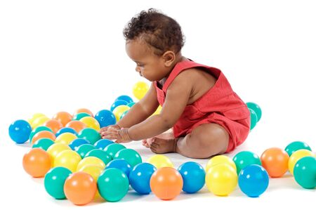 Adorable  girl playing with balls of colors photo