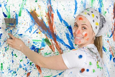 Attractive woman painting the background of many colors photo