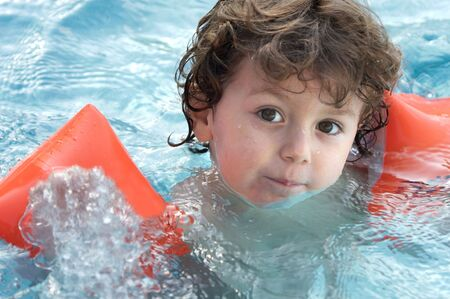 floater: photo of an adorable boy learning to swim Stock Photo