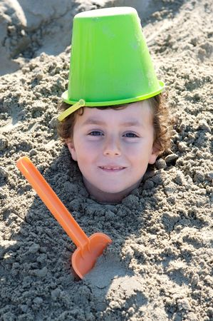 Small child buried in the sand of the beach photo