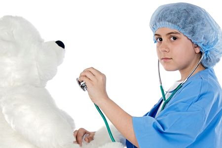 Little doctor examining her teddy a over white background photo