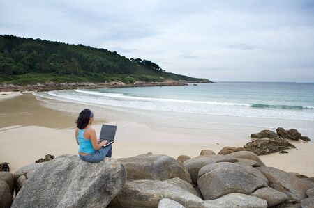 woman with laptop computer on the beach photo
