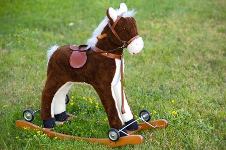 rein: Small wooden toy horse on the grass