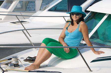 aboard: Beautiful woman aboard a yacht sunbathing with sunglasses
