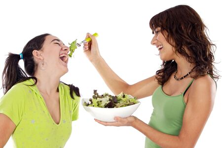 jokes: Two beautiful girls playing with a salad a over white background Stock Photo