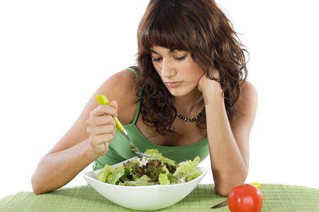 caras tristes: Un adolescente triste comer ensalada. Cuidado de su dieta.