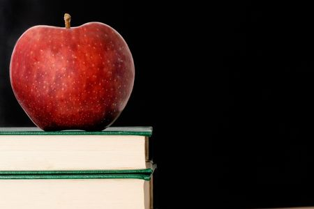 A red apple red on a green book on a black background photo