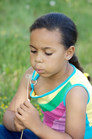 African little girl blowing one dandelion sitting on the field   photo