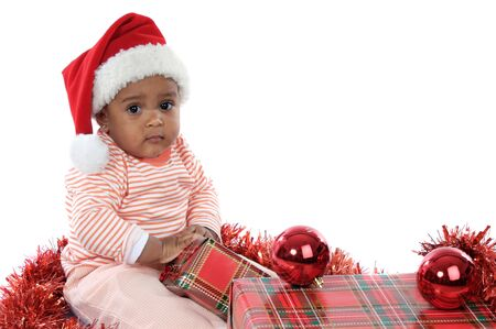 holding a christmas ornament: Adorable baby girl with christmas presents and santa hat Stock Photo