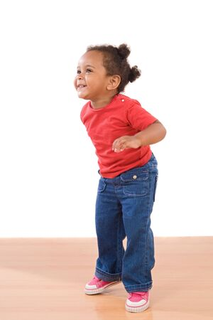 African baby girl on tiptoe on a over wooden floor Stock Photo