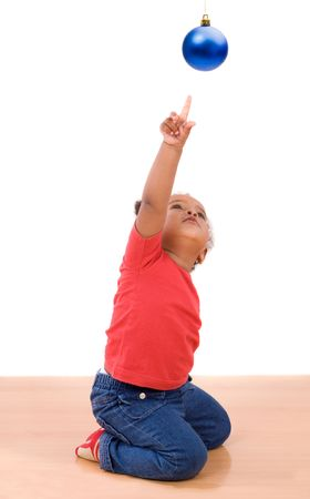 African baby girl pointing one ball of Christmas kneel over wooden floor Stock Photo - 3817843