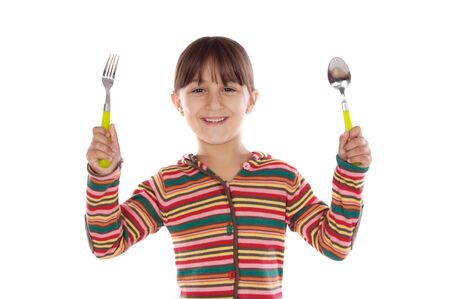 Adorable girl with fork and spoon ready to lunch on a over white background photo
