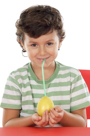 Adorable boy drinking juice of lemon on a over white background photo