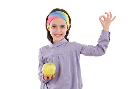 Adorable girl with a apple saying OK on a white background photo