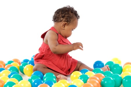 Adorable baby girl playing with balls of colors Stock Photo