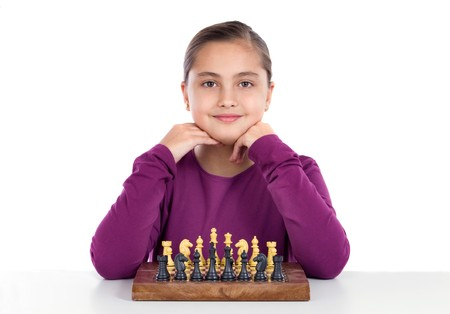 Attractive little girl playing chess on a over white background photo