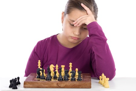 Worried little girl playing chess on a over white background photo