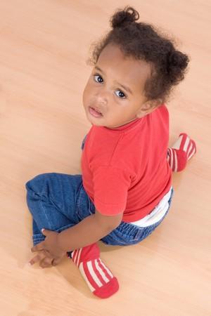 Adorable african baby sit over wooden floor Stock Photo