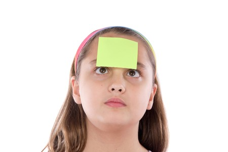 squint: Adorable girl squint with post-it in her front isolated over white