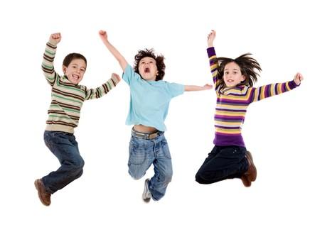 boy jumping: Tres ni�os felices a la vez de saltar sobre un fondo blanco Foto de archivo