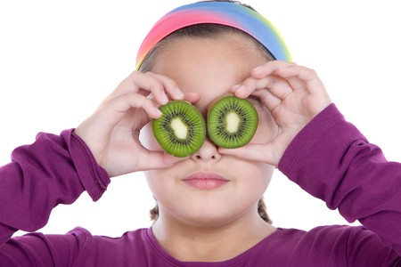 Cute girl playing with kiwi a over white background photo